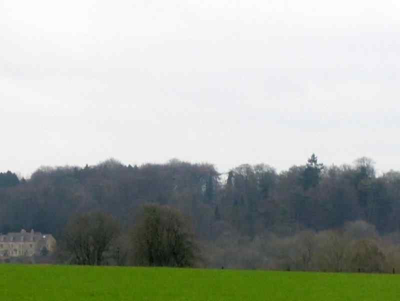 After crossing the River Frome we climb up through slithery woods and emerge on the hilltop to catch a distant view of Edgeworth Manor