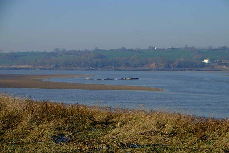 With the remains of the boats which destroyed the old bridge visible at  low tide