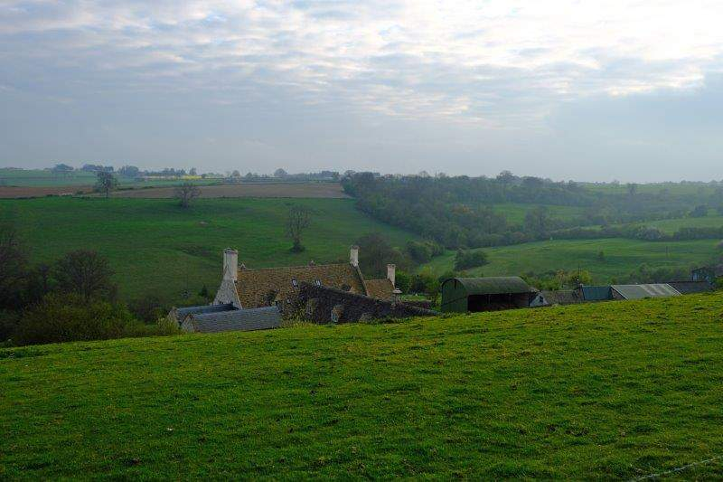 Farm tucked away under the brow of the hill