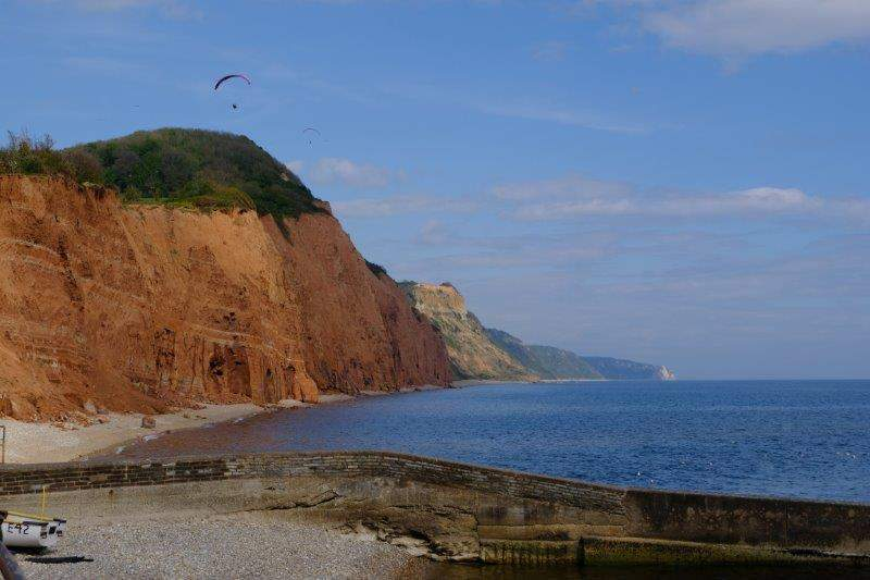 Now on the seafront we watch the hang gliders on the cliff tops