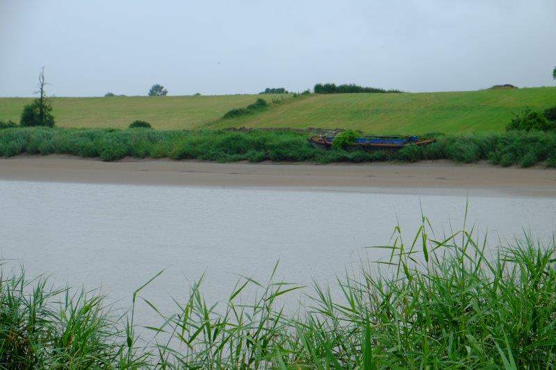 Reaching the banks of the Severn - an old barge beached on the other side