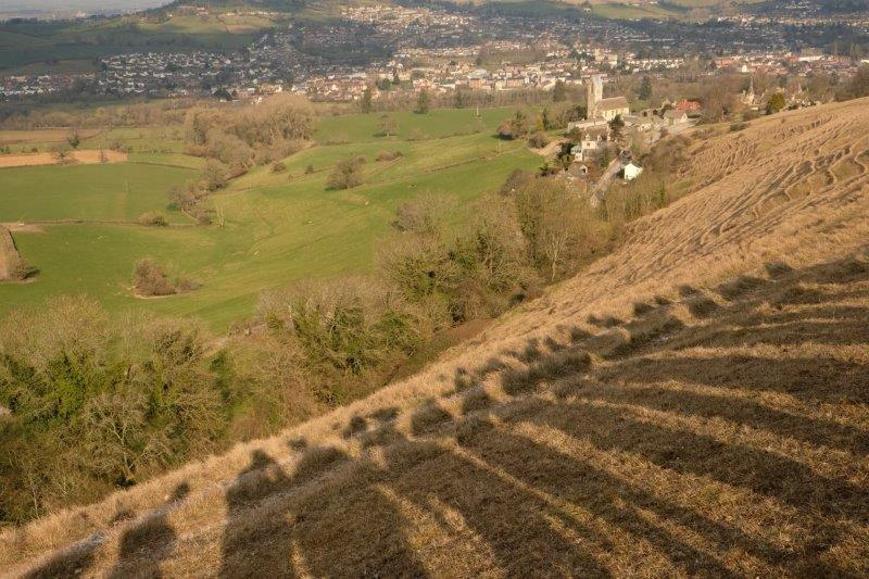 Casting shadows as we look down on Selsley Church