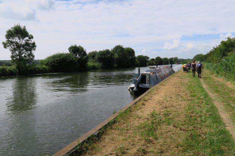 A canal boat tied up and owners relaxing on the shore