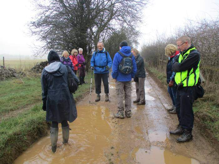 We reach a muddy track. Janet demonstrates the depth of the puddles