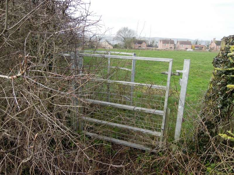 Coming on to Friday Street the kissing gate opposite is wired up and blocked with a thorny bush, and the signpost has been removed
