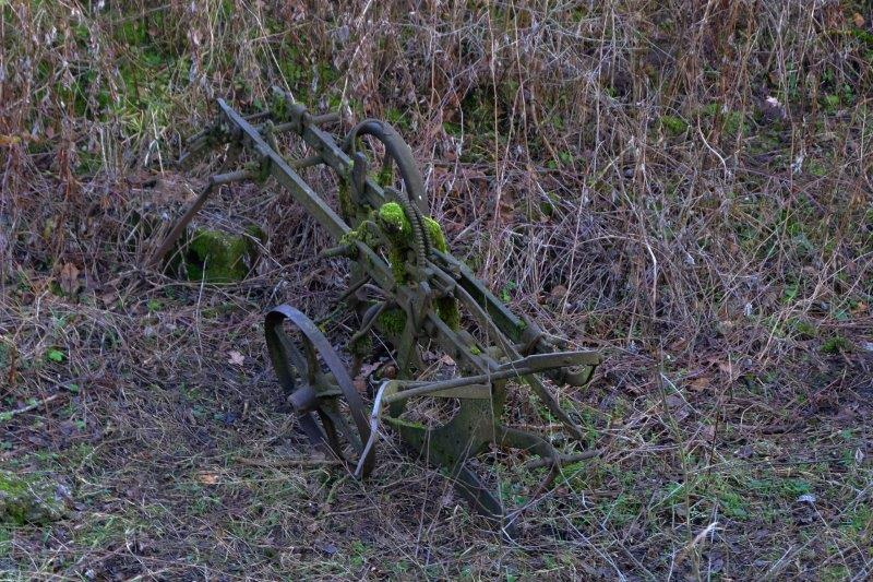 Old agricultural machinery on the dry canal bed