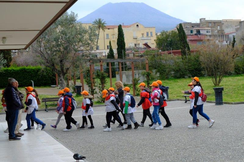 Schoolchildren lining up to go into Herculaneum. Vesuvius (closed because of the wind) in the  background, pigeon in the foreground