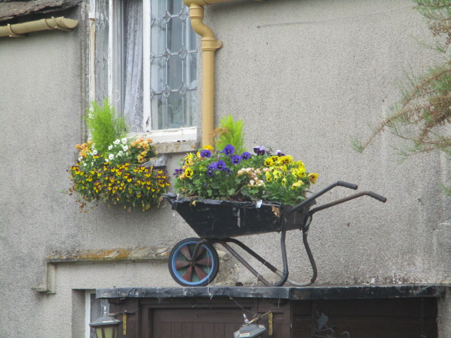Nice wheelbarrow of flowers over the porch, but how do you get it there? Do you lift it up after planting, put there empty and ascend with earth and plants? A discussion (though short)